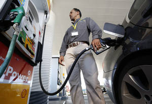 Photo - FILE - In this file photo taken Friday March 7, 2014, Eric Henry gases up his car in Sacramento, Calif. Drivers will get the slightest of breaks on gasoline prices this summer, according to the Energy Department. The national average price is forecast to fall — by just one cent — to $3.57 per gallon between April and September, the months when Americans do most of their driving. (AP Photo/Rich Pedroncelli, File)