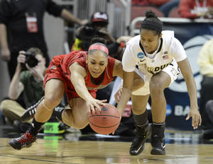 Photo - Louisville's Bria Smith, left, battles Purdue's April Wilson for a loose ball during the second half of their second round game in the women's NCAA college basketball tournament in Louisville, Ky., Tuesday March 26, 2013. Louisville defeated Purdue 76-63. (AP Photo/Timothy D. Easley)