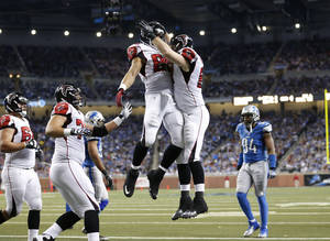 Photo - Atlanta Falcons tight end Michael Palmer, center right, celebrates his touchdown with tight end Tony Gonzalezduring the fourth quarter of an NFL football game against the Detroit Lions at Ford Field in Detroit, Saturday, Dec. 22, 2012. (AP Photo/Rick Osentoski)
