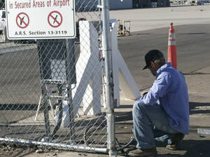 photo -   An unidentified worker makes repairs to a gate at Phoenix Sky Harbor International Airport Friday morning, Nov. 16, 2012, after a woman driving with a small child in her car crashed through the gate and drove on a runway Thursday night. The incident was the latest in a series of similar mishaps across the country that have raised questions whether the nation's airports are truly secure. (AP Photos/Jacques Billeaud)