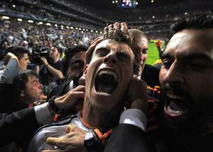 Photo - Real Madrid's Gareth Bale celebrates with teammates after scoring his side's second goal in the Champions League final soccer match against Atletico Madrid at the Luz Stadium in Lisbon, Portugal, Saturday, May 24, 2014. Real Madrid won 4-1 in extra time. (AP Photo/Manu Fernandez)