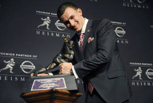 photo - Texas A&M quarterback Johnny Manziel poses with the Heisman Trophy after becoming the first freshman to win the award, Saturday, Dec. 8, 2012, in New York. (AP Photo/Henny Ray Abrams)