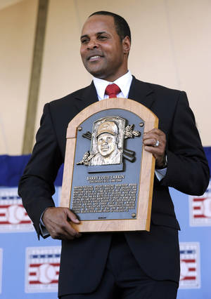 photo - FILE - In this July 22, 2012, file photo, former Cincinnati Reds star Barry Larkin holds his plaque after his induction into the National Baseball Hall of Fame and Museum during a ceremony in Cooperstown, N.Y. Larkin wants to keep baseball's most exclusive club clean.  Inducted into the Hall of Fame last summer, he told The Associated Press in a phone interview Wednesday, Dec. 5, 2012, that players who cheat shouldn't receive baseball's highest individual honor. (AP Photo/Tim Roske, FIle)