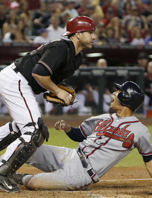 Photo - Atlanta Braves' Andrelton Simmons, right, shouts at the umpire as he scores ahead of the tag by Arizona Diamondbacks' Miguel Montero during the third inning of a baseball game Saturday, June 7, 2014, in Phoenix. (AP Photo/Ross D. Franklin)