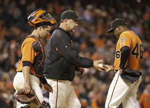 Photo - San Francisco Giants relief pitcher Santiago Casilla, right, hands the ball to manager Bruce Bochy, center, and heads for the dugout as catcher Buster Posey, left, looks on in the ninth inning of a baseball game against the Miami Marlins Friday, May 16, 2014, in San Francisco. Miami won the game 7-5 and Casilla was the losing pitcher. (AP Photo/Eric Risberg)