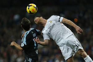 Photo - Real Madrid's Xabi Alonso, left, in action with Celta's Jonathan Castro 'Jonny', right, during a Spanish La Liga soccer match between Real Madrid and Celta at the Santiago Bernabeu stadium in Madrid, Spain, Monday, Jan. 6, 2014. (AP Photo/Andres Kudacki)