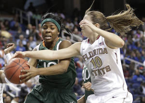 photo - Miami's Michelle Woods, left, and Florida State's Leonor Rodriguez, right, battle for a rebound during the first half of an NCAA college basketball game at the Atlantic Coast Conference tournament in Greensboro, N.C., Friday, March 8, 2013. (AP Photo/Chuck Burton)