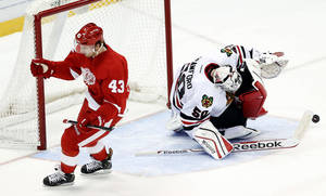Photo - Detroit Red Wings center Darren Helm (43) celebrates scoring a goal against Chicago Blackhawks goalie Corey Crawford (50) in a shootout during an NHL hockey game Wednesday, Jan. 22, 2014, in Detroit. Detroit won 5-4. (AP Photo/Paul Sancya)