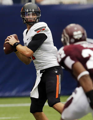 Photo - Oklahoma State's J.W. Walsh (4) looks to pass during the AdvoCare Texas Kickoff college football game between the Oklahoma State University Cowboys (OSU) and the Mississippi State University Bulldogs (MSU) at Reliant Stadium in Houston, Saturday, Aug. 31, 2013. OSU won, 21-3. Photo by Nate Billings, The Oklahoman