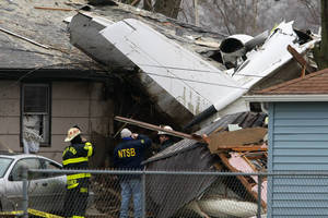 photo - A National Transportation Safety Board investigator and South Bend firefighters early Monday, March 18, 2013, survey the scene of Sunday's fatal plane crash, along Iowa Street in South Bend, Ind. Photo by James Brosher, South Bend Tribune/AP <strong>James Brosher - AP</strong>