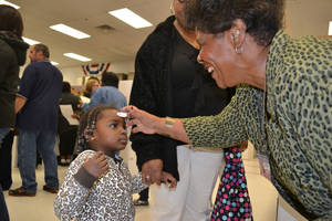 "Photo - Pat Harris, inspector for the Oklahoma County Election Board, stamps an ""I Voted"" sticker on the forehead of Kamora Beard, 3, during the second day of early voting Saturday. <strong>Zeke Campfield - The Oklahoman</strong>"