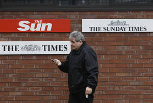 Photo - FILE - In this Friday, Feb. 17, 2012 file photo, a man walks past signs of Rupert Murdoch's News International's titles, outside their headquarters in London. News Corp. is reporting their fourth quarter 2012 earnings on Wednesday, Feb. 6, 2013. (AP Photo/Lefteris Pitarakis, File)