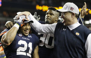 Photo - Auburn running back Tre Mason (21) and Auburn head coach Gus Malzahn celebrate after the second half of the Southeastern Conference NCAA football championship game against the Missouri, Saturday, Dec. 7, 2013, in Atlanta. Auburn won 59-42. (AP Photo/John Bazemore)