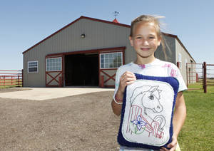 Photo - Sarah Meachan, 9, holds a horse pillow she saved from the tornado that hit Peppers Ranch a year ago Thursday. Three horses were killed, and the barn destroyed. PHOTOS BY DAVID MCDANIEL, THE OKLAHOMAN