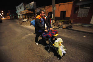 Photo - A man pushing a baby leaves his home as he walks to a safe area after a strong aftershock in Arica, Chile, early Thursday, April 3, 2014. A powerful 7.8-magnitude aftershock hit Chile's far-northern coast late Wednesday night, shaking the same area where a magnitude-8.2 earthquake hit just a day before causing some damage and six deaths. (AP Photo/Luis Hidalgo)