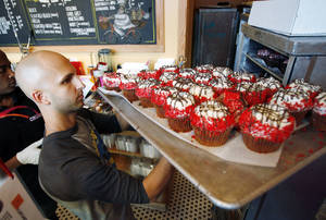 Photo - FILE - In this Sept. 20, 2007 file photo, Crumbs Bake Shop managing partner Harley Bauer carries of tray of cupcakes during the store's grand opening in Beverly Hills, Calif. Crumbs on Monday, July 7, 2014 said it is shuttering all its stores, a week after the struggling cupcake shop operator was delisted from the Nasdaq. (AP Photo/Matt Sayles, File)