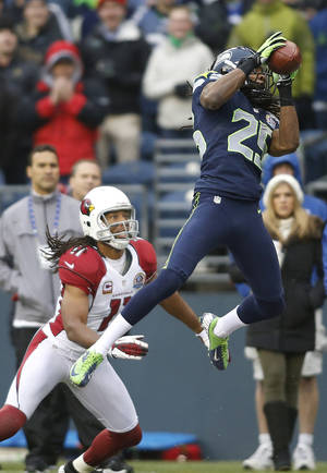 Photo - Seattle Seahawks cornerback Richard Sherman (25) intercepts a pass in front of Arizona Cardinals wide receiver Larry Fitzgerald (11) which was returned for a 19-yard touchdown during the second quarter of an NFL football game in Seattle, Sunday, Dec. 9, 2012. (AP Photo/John Froschauer)