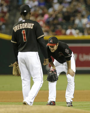 Photo - Arizona Diamondbacks pitcher Wade Miley, right, rests after being hit with a line drive against the San Diego Padres during the fourth inning of a baseball game, Saturday, May 25, 2013, in Phoenix. Looking on is Didi Gregorius.  (AP Photo/Matt York)