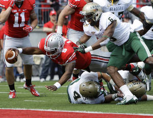photo -   Ohio State's Braxton Miller, left, scores a touchdown against Alabama-Birmingham's Jake Genus, bottom, and Lamar Johnson (6) during the second quarter of an NCAA college football game Saturday, Sept. 22, 2012, in Columbus, Ohio. (AP Photo/Jay LaPrete)