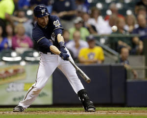 Photo - Milwaukee Brewers' Jonathan Lucroy hits a two-run single during the first inning of a baseball game against the Pittsburgh Pirates Tuesday, Sept. 3, 2013, in Milwaukee. (AP Photo/Morry Gash)