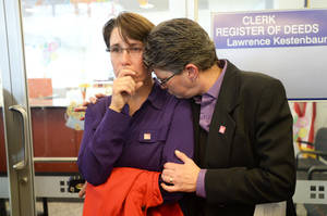 Photo - Dana Bauer, right, comforts her partner Tracy Pennington, left, after the couple learned they would not be able to apply for a marriage license at Washtenaw County Clerk's Office on Wednesday, Oct. 16, 2013, in Ann Arbor, Mich. U.S. District Judge Bernard Friedman said he won't make a decision until after hearing testimony Feb. 25 from experts on whether there is a legitimate state interest in banning gay marriage. (AP Photo/The Ann Arbor News, Melanie Maxwell)