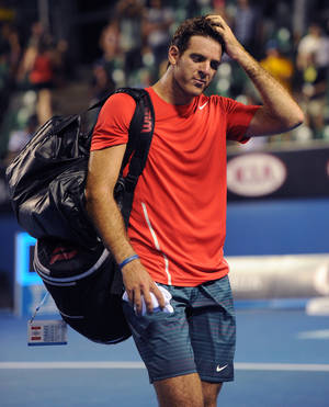 Photo - Juan Martin del Potro of Argentina walks from the court after losing to Roberto Bautista Agut of Spain in their second round match at the Australian Open tennis championship in Melbourne, Australia, Thursday, Jan. 16, 2014. (AP Photo/Andrew Brownbill)