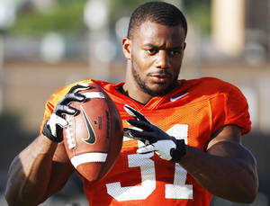 Photo - OKLAHOMA STATE UNIVERSITY / OSU / COLLEGE FOOTBALL: Oklahoma State running back Jeremy Smith throws the ball during downtime of the first full pad practice of the fall on August 6, 2013. Photo by KT King/ for The Oklahoman