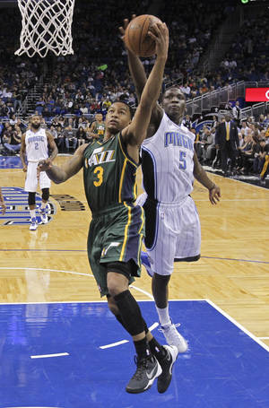 Photo - Orlando Magic's Victor Oladipo (5) blocks a shot by Utah Jazz's Trey Burke (3) during the first half of an NBA basketball game in Orlando, Fla., Wednesday, Dec. 18, 2013. (AP Photo/John Raoux)