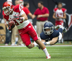 Photo - Houston wide receiver Andrew Rodriguez gets past Rice safety Garrett Fuhrman during the first half of an NCAA college football game Saturday, Sept. 21, 2013, in Houston. (AP Photo/Houston Chronicle, Smiley N. Pool) MANDATORY CREDIT