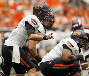 Photo - Oklahoma State's Clint Chelf (10) gives instructions to his team at the line of scrimmage in the first quarter during the AdvoCare Texas Kickoff college football game between the Oklahoma State University Cowboys (OSU) and the Mississippi State University Bulldogs (MSU) at Reliant Stadium in Houston, Saturday, Aug. 31, 2013. Photo by Nate Billings, The Oklahoman