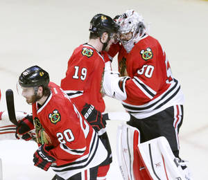 Photo - Chicago Blackhawks goalie Corey Crawford, right, celebrates the Blackhawks' 3-1 win over the Los Angeles Kings with Jonathan Toews (19) and Brandon Saad (20) after Game 1 of the Western Conference finals in the NHL hockey Stanley Cup playoffs in Chicago on Sunday, May 18, 2014. The Blackhawks won 3-1. (AP Photo/Charles Rex Arbogast)
