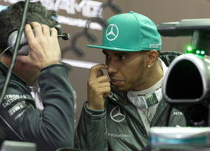 Mercedes driver Lewis Hamilton of Britain chats with his crew inside the garage during the practice session ahead of Sunday's Chinese Formula One Grand Prix at Shanghai International Circuit in Shanghai, China Friday, April 18, 2014. (AP Photo/Andy Wong)