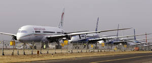 photo - A line of 787 jets are parked Thursday, Jan. 17, 2013, at Paine Field in Everett, Wash. Federal officials say they are temporarily grounding Boeing's 787 Dreamliners until the risk of possible battery fires is addressed. The Federal Aviation Administration said Wednesday it will issue an emergency safety order requiring U.S. airlines to temporarily cease operating the 787, Boeing's newest and most technologically advanced plane. (AP Photo/Elaine Thompson)