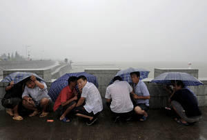 photo -   Chinese visitors shelter under umbrellas in the rain while waiting for the Qiantang River tides on the river bank in Haining in east China's Zhejiang province Thursday, Aug. 2, 2012. Typhoon Saola is expected hit eastern China, after moving across Philippines and Taiwan. (AP Photo) CHINA OUT