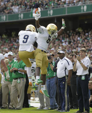 Photo -   Notre Dame's Theo Riddick, right, reacts with Louis Nix III after scoring a touchdown against the Navy's during their NCAA college football game in Dublin, Ireland, Saturday, Sept. 1, 2012. (AP Photo/Peter Morrison)