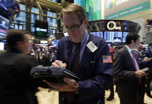 Photo - Trader Luke Scanlon works on the floor of the New York Stock Exchange Thursday, Oct. 10, 2013.  World stock markets fell Wednesday, Oct. 23, 2013 hit by slower U.S. hiring and reports of tighter money market conditions in China that could check its economic recovery. (AP Photo/Richard Drew)