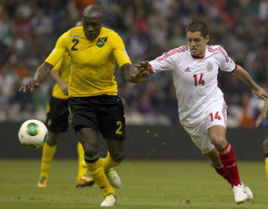 photo - Jamaica's Nyron Nosworthy, left, fights for the ball with Mexico's Javier Hernandez, center, during a 2014 World Cup qualifying soccer match in Mexico City, Wednesday, Feb. 6, 2013. (AP Photo/Eduardo Verdugo)