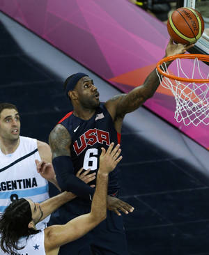 Photo -   United States' Lebron James (6) shoots for the basket past Argentina's Juan Gutierrez, left, and Argentina's Luis Scola, bottom, during a men's basketball semifinal game at the 2012 Summer Olympics, Friday, Aug. 10, 2012, in London. (AP Photo/Victor R. Caivano)