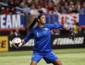 Photo - USA goalkeeper Hope Solo clears the ball in the first half of an exhibition soccer match against Russia, Thursday, Feb. 13, 2014, in Atlanta. (AP Photo/John Bazemore)