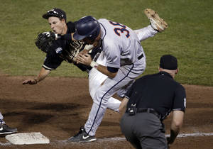 Photo - Vanderbilt third baseman Tyler Campbell, rear, collides with Virginia's Mike Papi as he tags out Papi in the ninth inning of Game 2 of the best-of-three NCAA baseball College World Series finals in Omaha, Neb., Tuesday, June 24, 2014. (AP Photo/Nati Harnik)