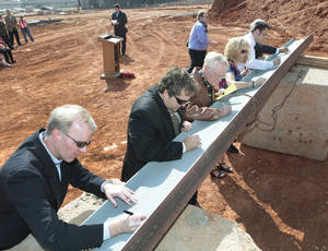 photo - School board members sign the last piece of structural steel Tuesday during Deer Creek Public Schools' topping-out ceremony for the Deer Creek Performing Arts and Athletic Center.  Photos by David McDaniel, The Oklahoman