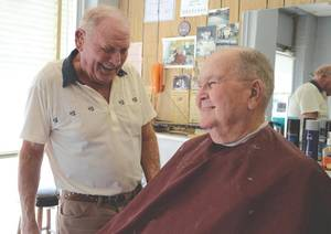 Photo - Jack Cisco (left) shares a story and a laugh with customer Wendell Allen at Jack's Barber Shop in Enid. (Enid News & Eagle photo)