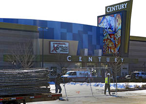 "Photo - Workers with American Fence remove the fence from around the Century theater in Aurora, Colo., on Thursday, Jan. 17, 2013.  The Colorado movie theater where a gunman killed 12 people and wounded dozens of others reopens Thursday with a private ceremony for victims, first responders and officials.   Theater owner Cinemark plans to temporarily reopen the entire 16-screen complex in Aurora to the public on Friday, then permanently on Jan. 25. Aurora's mayor, Steve Hogan, has said residents overwhelmingly support reclaiming what he calls ""an important venue for Aurora.""  (AP Photo/Ed Andrieski)"