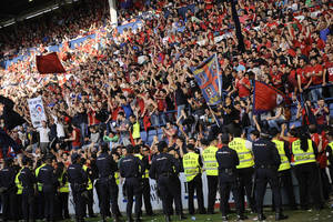 Photo - Line of policemen control Osasuna's supporters after one fence of the stadium was broken while people celebrated a goal of their team, during their last  Spanish League soccer match between Osasuna and Betis,, at El Sadar stadium, in Pamplona northern Spain, Sunday, May 18, 2014. Five people was injured. (AP Photo/Alvaro Barrientos)