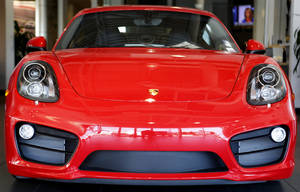 Photo - A red Porsche Cayman S shines in the Bob Moore Porsche Audi showroom in Oklahoma City. The dealer is working on bringing more high-end luxury vehicle brands to the metro. Photo by Steve Gooch, The Oklahoman <strong>Steve Gooch</strong>