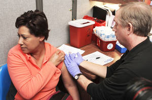 photo - Karen Woodard, of Oklahoma City, receives a flu vaccination at the Oklahoma City-County Health Department.  PAUL HELLSTERN, The Oklahoman