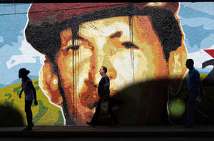 photo -   People walk past a mural depicting Venezuela's President Hugo Chavez, in Caracas, Venezuela, Monday, Oct. 8, 2012. Chavez won re-election and a new endorsement of his socialist project Sunday, surviving his closest race yet after a bitter campaign against opposition candidate Henrique Capriles. (AP Photo/Rodrigo Abd)