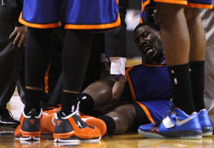 Photo -   New York Knicks' Iman Shumpert, center, is helped up from the court after an injury in the second half during an NBA basketball game against the Miami Heat in the first round of the Eastern Conference playoffs in Miami, Saturday, April 28, 2012. (AP Photo/Lynne Sladky)