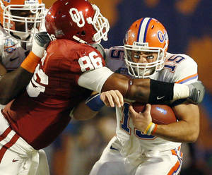 Photo - Oklahoma's Adrian Taylor, left, hits Florida's Tim Tebow at the line of scrimmage during the first half of BCS Championship on Jan. 8, 2009. Tebow and the Gators scored only 24 points in their victory over the Sooners, which was far below their scoring average for the season. PHOTO BY BRYAN TERRY, THE OKLAHOMAN Archives