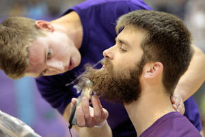 photo - Junior Brenner Milburn shaves the beard of senior Parker Stewart as a fundraiser for BALTO during an assembly at Edmond North High School on Friday. Photos By David McDaniel, The Oklahoman